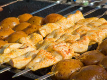 Appetizing delicious fried meat and potatoes on a barbecue grill outdoors. Royalty Free Stock Photo