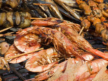 Appetizing delicious fried seafood, fish, shrimp on a barbecue grill outdoors. Stock Photography