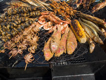Appetizing delicious fried seafood, fish, shrimp, octopus, mussels on a barbecue grill outdoors. Stock Images