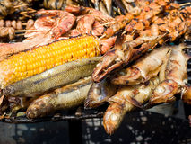 Appetizing delicious fried seafood, fish, shrimp, octopus, mussels on a barbecue grill outdoors. Royalty Free Stock Image