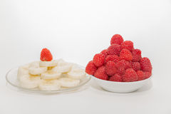 Appetizing, delicious sliced banana and raspberry in ceramic plates on grey Stock Photos