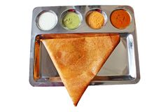 Appetizing,delicious triangular Indian masala dosa. Appetizing and delicious traingular Indian masala dosa in golden brown color with 3 types of chutney and Stock Photos