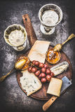Appetizing fine cheese selection on rustic plate with wine, grape and Honey mustard sauce Royalty Free Stock Images
