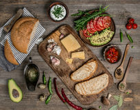 Appetizing foods served on wooden table, topview. Avocado, cheese, bread and tomatoes, appetizing foods served on wooden table, topview Royalty Free Stock Photos