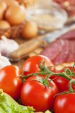 Appetizing foods ( twig red. Tomatoes,lettuce, garlic, sausage, eggs and seasonings) background table Stock Photography