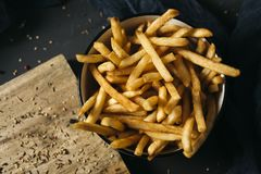 Appetizing french fries in a bowl. High angle shot of some appetizing french fries served in a white ceramic bowl, placed on a dark gray rustic wooden table stock photos