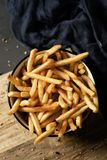 Appetizing french fries in a bowl. High angle shot of some appetizing french fries served in a white ceramic bowl, placed on a dark gray rustic wooden table royalty free stock photos