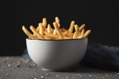 Appetizing french fries in a bowl. Some appetizing french fries served in a white ceramic bowl, placed on a gray rustic wooden table, against a black background stock photography