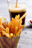Appetizing french fries in a metallic basket. Closeup of some appetizing french fries served in a metallic basket, a glass with soda and a bowl with ketchup, on Royalty Free Stock Photography