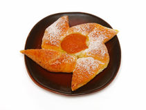 Appetizing fresh-baked pastry on saucer. Golden cookie with apricot on a plate isolated on white Stock Image