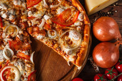 Appetizing fresh pizza on rustic table. Fast food. Traditional italian cuisine. Delicious tasty pizza with tomatoes, chicken and onion cut into slices on wooden Royalty Free Stock Images
