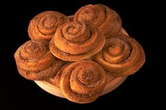 Appetizing fresh rolls with ci. Nnamon and sugar on a wooden plate isolated on black background Stock Photo