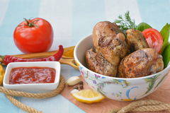 Appetizing fried chicken with tomato sauce and spices. Fried chicken legs, wings with tomato sauce - appetizing snack Royalty Free Stock Images