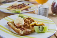 Appetizing fried golden Belgian waffle with pieces of fresh banana, kiwi, kumquat and maple syrup on a striped earthenware plate. Appetizing fried golden stock image