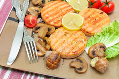 Appetizing fried medallions of salmon, stuffed snails with mushr Royalty Free Stock Images
