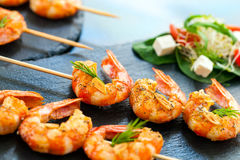 Appetizing giant shrimp starter. Extreme close up of char grilled giant shrimp starter mounted on wood skewers Royalty Free Stock Photography