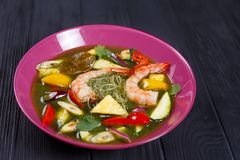 Appetizing green curry soup with prawns and rice noodles, close stock photos