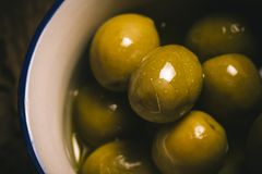 Appetizing green salted olives i a rustic bowl Stock Image