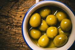 Appetizing green salted olives on old wooden table Stock Photo