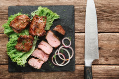 Appetizing grill meal. Kebab served on wood table. Tasty shashlik served with green salad and onion rings on black slate with big knife, on rustic wooden table Royalty Free Stock Photos