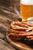 Appetizing grill sausages and light beer, close up. German food, Oktoberfest menu. Mug of cold light beer and wooden platter with various grilled sausages, close Royalty Free Stock Photos