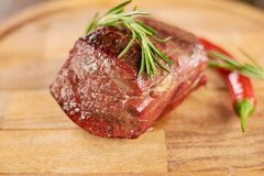 Appetizing grilled beef steak. Beef steak medium grilled with rosemary and red chili pepper. Delicious food on wooden background Stock Images