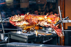 Appetizing grilled lamb on the spit. Roasted pig on the traditional barbecue. Roasting barbecue is prepared of a ram, lamb Stock Images