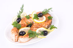 Appetizing Grilled Salmon. With lemon, black olives and mixed greens isolated over white Stock Photos
