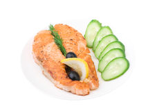 Appetizing Grilled Salmon with sliced cucumber. Lemon and black olives isolated over white Royalty Free Stock Images