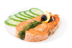 Appetizing Grilled Salmon with sliced cucumber. Lemon and black olives isolated over white Stock Photos