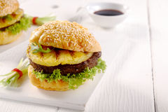 Appetizing Hawaiian Burger on a White Table Stock Photo