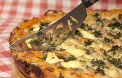 Appetizing homemade pizza and original knife Stock Photo