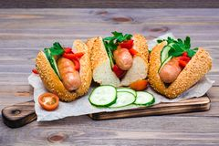 Appetizing hot dogs from fried sausages, sesame buns and fresh vegetables on a cutting board royalty free stock photo