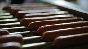 Appetizing hotdog sausages being cooked on grill, snacks at street food festival. Stock footage stock video