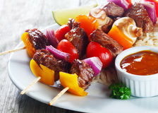 Appetizing Kebab on Plate with Tomato Sauce stock photo