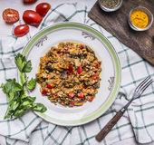 Appetizing lamb vegetables on a white plate with tomato and parsley seasoned and fork on a checkered napkin top view close up Royalty Free Stock Image