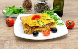 Appetizing lasagna with tomato and olives on a plate. stock images