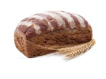 A homemade black bread, next to several spikelets of wheat. Appetizing loaf of homemade black bread, sprinkled with flour from above, next to several golden royalty free stock photos