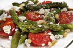 Appetizing Mediterranean salad. Close up of appetizing Mediterranean salad with asparagus, tomatoes, and feta cheese Royalty Free Stock Image