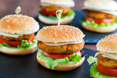 Appetizing mini chicken burgers. Extreme close up of multiple Appetizing mini chicken burgers. Small burgers in row for catering service Royalty Free Stock Photos
