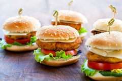 Appetizing mini chicken burgers on wooden surface. Macro close up of multiple appetizing mini chicken burgers on wooden surface royalty free stock photos
