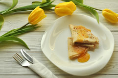 Appetizing pancakes with fruit jam, a cup of tea with lemon, yellow tulips, fork and knife Royalty Free Stock Photo