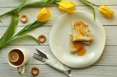 Appetizing pancakes with fruit jam, a cup of tea with lemon, yellow tulips, fork and knife Stock Image