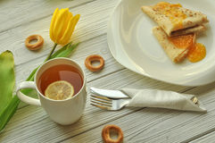 Appetizing pancakes with fruit jam, a cup of tea with lemon, yellow tulips, fork and knife Stock Photo