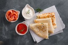 Appetizing pancakes with salmon, caviar and sour cream royalty free stock photography