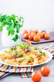Appetizing pasta with fried mushrooms and fresh herbs on a plate. Cherry tomatoes and parsley in a glass on a table Stock Images