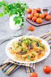 Appetizing pasta with fried mushrooms and fresh herbs on a plate. Cherry tomatoes and parsley in a glass on a table Royalty Free Stock Images