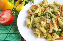 Appetizing pasta with vegetables and cheese on a white plate close-up stock images