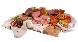 Appetizing piece of smoked meat with olive and a sprig of dill pinned on a fork against a black stone wall . stock images