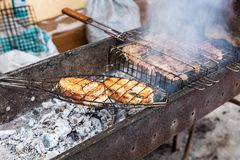 Pieces of grilled fish and meat cooked on the grill Royalty Free Stock Photography